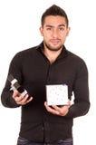 Reizend junger Mann, der ein Geschenkboxschauen hält Stockbild
