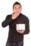 Reizend junger Mann, der ein Geschenkboxschauen hält Stockfotografie
