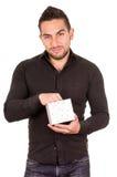 Reizend junger Mann, der ein Geschenkboxschauen hält Stockfoto