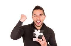 Reizend junger Mann, der eine Geschenkbox hält Lizenzfreie Stockfotos