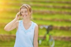 Reizend junges blondes Frauen-Nahaufnahme-Porträt im blauen Kleid sprechen Lizenzfreie Stockfotos