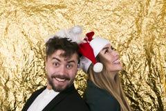 Reizend junges Mädchen in Weihnachtsmann-Hut und in bärtigem St. des jungen Mannes Lizenzfreies Stockbild