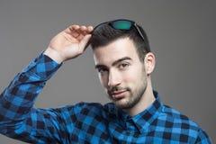 Reizend junges vorbildliches tragendes kariertes Hemd setzte Sonnenbrille in Haar ein Stockbilder