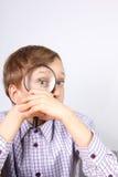 Reizend blonder kaukasischer Junge im purpurroten Hemd, das durch eine Lupe in der Verwunderung schaut Lizenzfreie Stockfotos