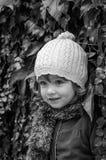 Reizend Kind des kleinen Mädchens in einem Hut und in einem Mantel, die gegen die Wand mit dem sonnigen Herbsttag der wilden Trau Lizenzfreies Stockfoto