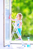 Reizend kleines Mädchen, das ein Fenster wäscht Lizenzfreies Stockbild