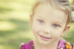 Reizend kleines Mädchen der blauen Augen mit träumerischem Blick Lizenzfreies Stockfoto