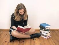 Reizend Mädchen, das auf dem Bretterboden und dem Lesebuch sitzt Lizenzfreie Stockfotos