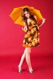 Reizend Mädchen, das im Kleid mit Regenschirm sitzt lizenzfreies stockfoto