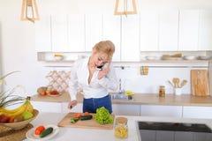 Reizend Mädchen, das am Telefon spricht und Abendessen in stilvollem k vorbereitet Lizenzfreies Stockbild