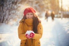 Reizend Mädchen in einer gelben Jacke und in einer roten Kappe wirft Schnee in der Luft Lizenzfreies Stockfoto