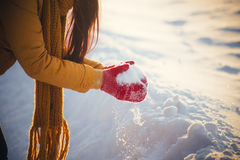 Reizend Mädchen in einer gelben Jacke und in einer roten Kappe wirft Schnee in der Luft Stockfoto
