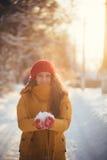 Reizend Mädchen in einer gelben Jacke und in einer roten Kappe wirft Schnee in der Luft Stockfotos