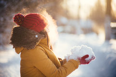 Reizend Mädchen in einer gelben Jacke und in einer roten Kappe wirft Schnee in der Luft Stockbilder