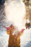 Reizend Mädchen in einer gelben Jacke und in einer roten Kappe wirft Schnee in der Luft Stockfotografie