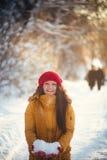 Reizend Mädchen in einer gelben Jacke und in einer roten Kappe wirft Schnee in der Luft Lizenzfreies Stockbild