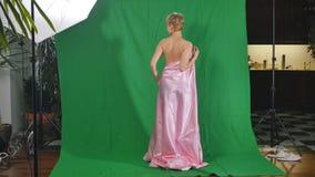 Reizend Mädchen in rosa Satin Bedsheet wirft für Kamera am grünen Hintergrund auf stock footage