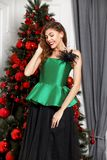 Reizend M?dchen gekleidet in einer stilvollen gr?nen Seidenspitze, schwarze Tellerrockhaltungen nahe bei dem Baum des neuen Jahre lizenzfreie stockfotografie
