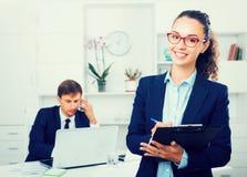 Reizend Manager der jungen Frau, der Pappe im Büro hält lizenzfreie stockbilder
