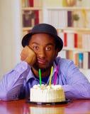 Reizend Mann, der blaues Hemd und den Hut sitzt durch Tabelle mit Geburtstagskuchen in der Front, das traurige deprimierte Feiern Lizenzfreies Stockfoto