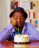 Reizend Mann, der blaues Hemd und den Hut sitzt durch Tabelle mit Geburtstagskuchen in der Front, das traurige deprimierte Feiern Stockfotos