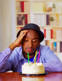 Reizend Mann, der blaues Hemd und den Hut sitzt durch Tabelle mit Geburtstagskuchen in der Front, das traurige deprimierte Feiern Lizenzfreie Stockfotos