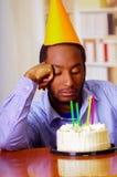 Reizend Mann, der blaues Hemd und den Hut sitzt durch Tabelle mit Geburtstagskuchen in der Front, das traurige deprimierte Feiern Stockbilder