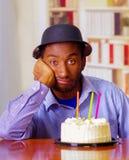 Reizend Mann, der blaues Hemd und den Hut sitzt durch Tabelle mit Geburtstagskuchen in der Front, das traurige deprimierte Feiern Stockfotografie