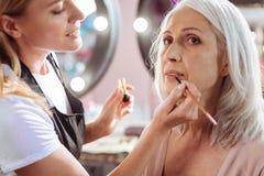 Reizend Maskenbildner, der oben das Make-up der Frau mit Lippenstift beendet Stockbilder