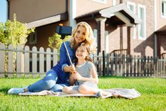 Reizend Mutter und Tochter, die selfies im Yard nimmt stockfotografie