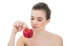 Reizend natürliches braunes behaartes Modell, das einen Apfel hält Stockfotos
