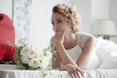 Reizend schöne Braut, die Hochzeitsblumenstrauß in ihren Händen hält Stockfotografie