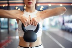 Reizend schönes Sportmädchen hebt eine Kesselglocke für exerc an stockfotos