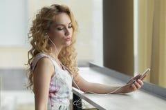 Reizend Schönheit ist hörende Musik durch ihren Smartphone am Kaffeestubecafé lizenzfreies stockbild