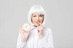 Reizend spielerische junge Frau, die Donut blinzelt und hält Lizenzfreie Stockfotos