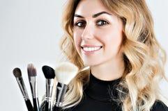 Reizend Stilist hält vier Berufsbürsten für das Anwenden von MA stockfoto