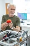 Reizend Vertretung des älteren Mannes druckte Tomate zu den Kollegen lizenzfreies stockbild