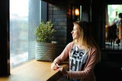 Reizend weibliche Person, die nahe Fenster am Café und am Träumen sitzt Lizenzfreie Stockfotografie