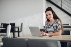 Reizend weiblicher Inhaber des Geschäfts nennend zur Managerüberwachungsarbeit des Angestellten sitzend im Caféinnenraum Stockfoto