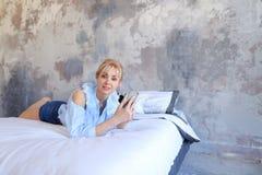 Reizend weibliches auf Kamera mit Telefon in der Hand aufwerfen und an liegen Lizenzfreies Stockfoto