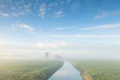 Reizend Windmühle durch Fluss am nebelhaften Morgen Lizenzfreie Stockbilder