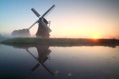 Reizend Windmühle durch See bei Sonnenaufgang Stockbild
