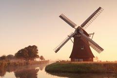 reizend Windmühle und Fluss bei Sonnenaufgang Stockfotografie