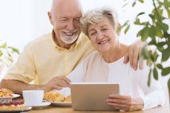 Reizende ältere Paare unter Verwendung der Tablette lizenzfreie stockfotografie