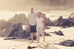 Reizende ältere reife Paare auf ihrem Gehen 60s oder 70s im Ruhestand glücklich und entspannt auf Strandseeufer in romantischem z Stockbild