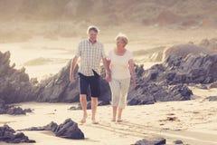 Reizende ältere reife Paare auf ihrem Gehen 60s oder 70s im Ruhestand glücklich und entspannt auf Strandseeufer in romantischem z Stockfotografie