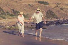 Reizende ältere reife Paare auf ihrem Gehen 60s oder 70s im Ruhestand glücklich und entspannt auf Strandseeufer in romantischem z Lizenzfreie Stockfotos