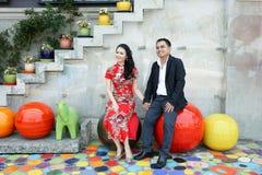 Reizende asiatische Paare, die Hand halten und auf bunten Kunststühlen sitzen Stockfotos