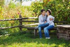 Reizende auf Bank sitzende und flirtende Paare Stockfotos