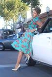 Reizende aufwerfende Frau und und um ein Weinlese-Auto Stockfoto
